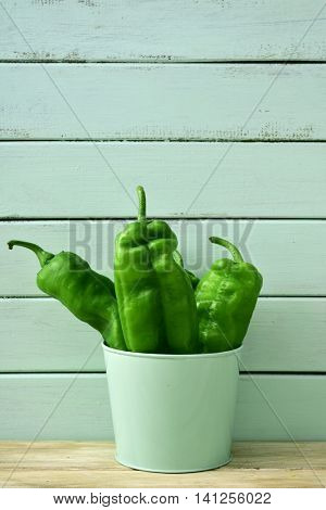 some raw green peppers in a pale green bucket on a rustic wooden table, against a pale green background