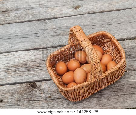 Brown eggs in the basket on a wooden table