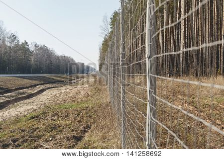 Protective mesh on the side of the road from wild animals. Road safety