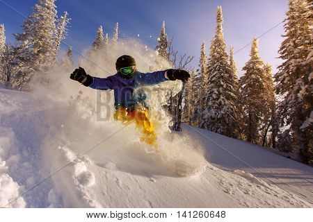 Snowboarder doing a toe side carve with deep blue sky in background