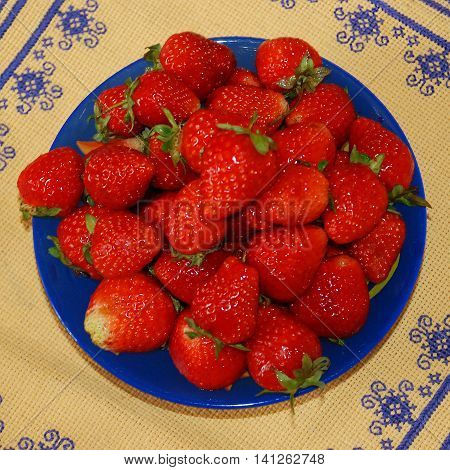 Red berries of strawberry in the blue plate, which stands on a yellow napkin