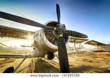 Old ruined biplane stands in the parking lot of an abandoned airfield. Dawn the sun's rays.