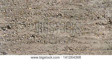 Close-up of a coarse made, gray concrete wall with partially exposed pebbles