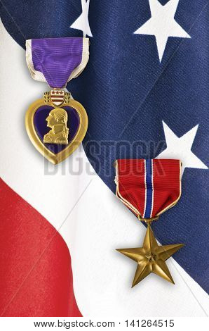 US Army Bronze Star and Purple Heart medals over a closeup on an American flag.