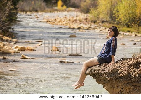 White water Mineral Creek stream in Colorado, USA during the fall with golden aspens and woman on edge dipping feet in water