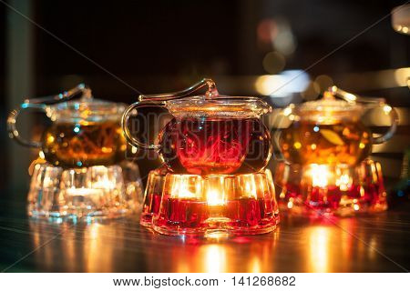 three glass teapots with candle heaters; cute transparent teakettles with fire heat;