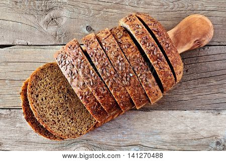 Loaf Of Sliced Whole Grain Bread With Flax Seeds, Above View On Wooden Background