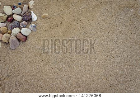 Beautiful sand background with stones. Beach sand background. Sandy texture with stones.. Brown sand. Background from fine sand. Sand background. Summer concept. Top view. Copy space.