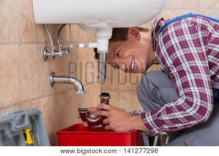 Happy Young Male Plumber Installing Sink Pipe In Bathroom