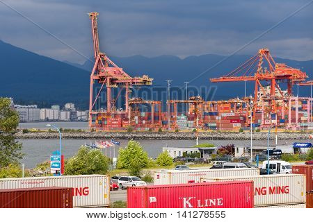 Vancouver Canada - July 23 2016: Container port at Vancouver harbor with wall of container in foreground. Two huge orange container cranes. Stacks of containers. Gray skies over dark mountains.
