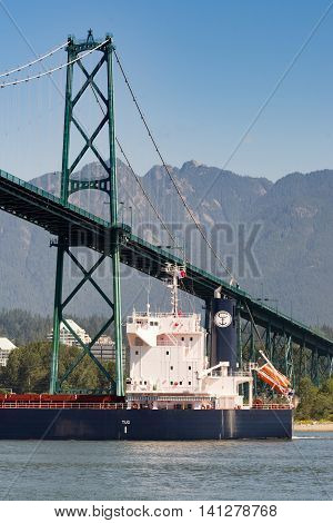 Vancouver Canada - July 24 2016: Bulk Ship passes under green Lions Gate bridge in Vancouver. Blue skies and mountains as background. Off Stanley Park.