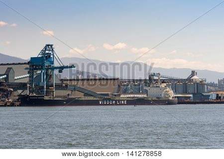 Vancouver Canada - July 24 2016: The Wisdom Line bulk carrier sits deep in the water as it loaded up. Harbor bulk loading installations and silos under clear skies.