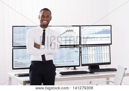 Portrait Of Happy Young Male Stock Market Broker In Office