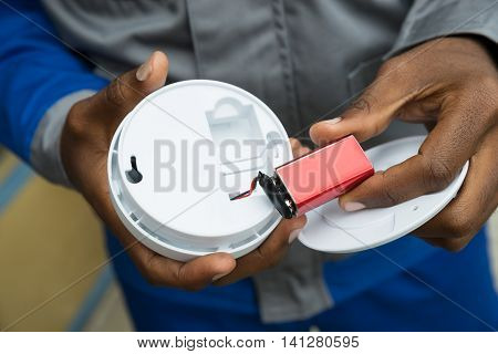 Close-up Of Electrician Hands Removing Battery From Smoke Detector