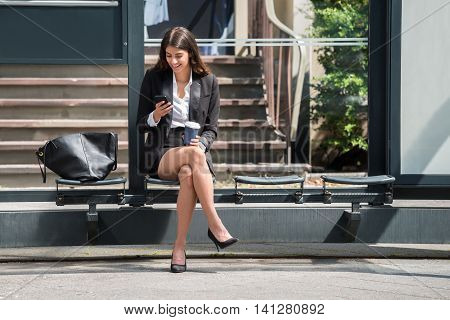 Happy Young Businesswoman With Disposal Cup Using Cellphone