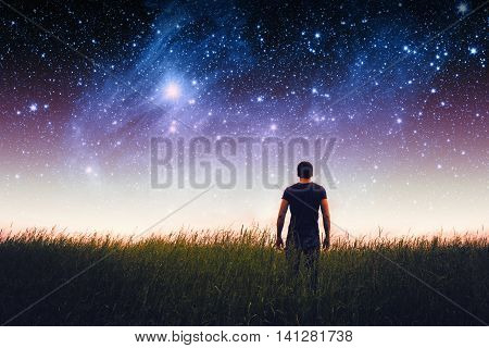Silhouette of young man on stars sky. Elements of this image furnished by NASA.