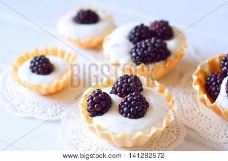Different size tartlets with cream and fresh dewberries. Sweet berry summer dessert.