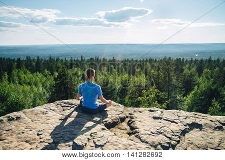 Man sitting on the top of the mountain in meditation session in Lotus Posture, padmasana, practicing pranayama.