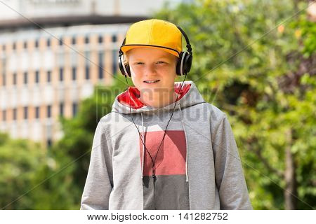 Portrait Of Smiling Boy Wearing Yellow Cap Listening To Music