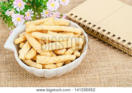 crunchy prawn crackers on cup wish diary on sack background.