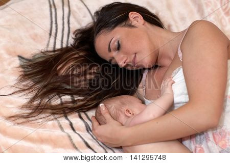 Young mum nurses the child on  on the house bed. Breastfeeding. poster