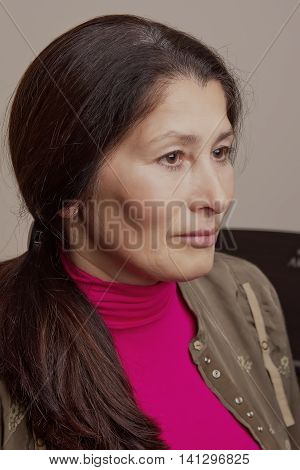 Portrait of a senior sad disoriented woman sitting on the chair