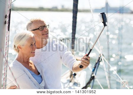 sailing, age, travel, technology and people concept - happy senior couple with smartphone selfie stick taking picture on sail boat or yacht deck floating in sea