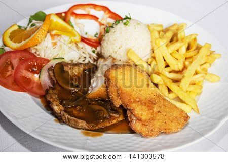 Festive menu of tasty chicken breast stuffed with ham and cheese with rice fries and pork with sauce and mushrooms. International cuisine. Food theme. Large portion. Close up photo.
