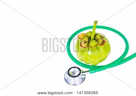 Close Up Garcinia Cambogia And Stethoscope On White Background.