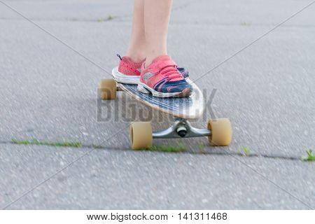 child skateboarding on urban background, kid's legs on longboard