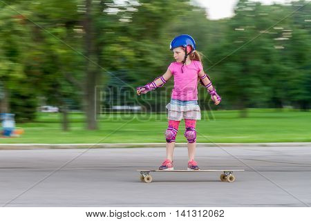 young girl skateboarding on natural background