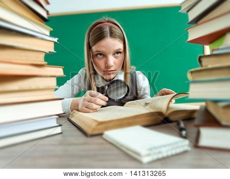 Unhappy teenage girl with magnifying glass surrounded by lots of books / photo of teen school girl creative concept with Back to school theme