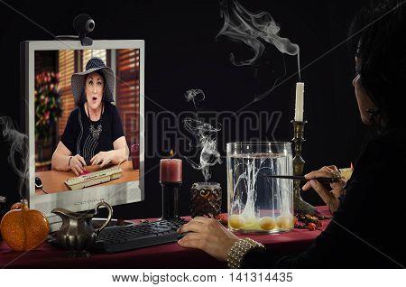 Psychic is doing egg divination in internet. Black haired fortune teller reads a shapes of egg whites in glass jar for older female client with shocked facial expression on monitor screen