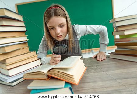 Inquisitive teenage girl reading a book / photo of teen school girl wearing glasses creative concept with Back to school theme