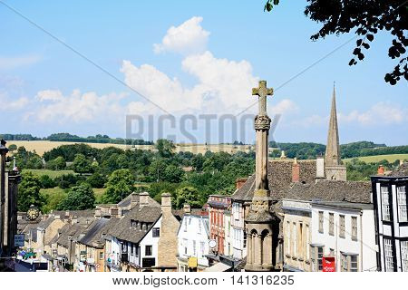 BURFORD, UNITED KINGDOM - JULY 20, 2016 - View of shops and businesses along The Hill shopping street with the war memorial in the foreground Burford Oxfordshire England UK Western Europe.
