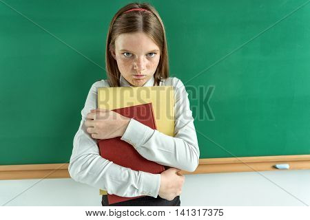 Upset little girl holding school books / photo of teen school girl creative concept with Back to school theme