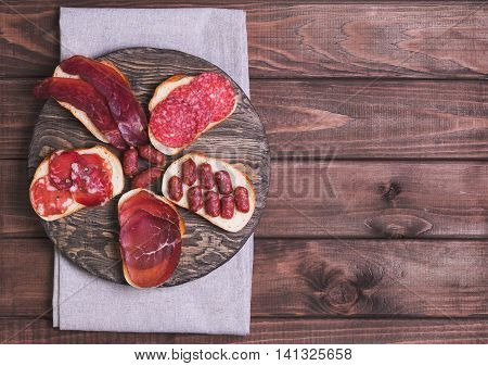 Several Sandwiches with Smoked and Jerked Meat and Sausage on Bread Wooden Brown Surface top view