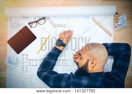 Young baldheaded african american young male designer with beard lying and sleeping on table with blueprint
