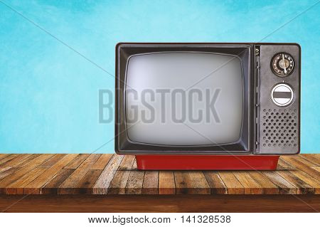 Old television on wood table. Vintage color tone style.