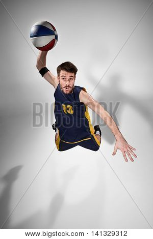 Full length portrait of a basketball player with a ball against gray studio background