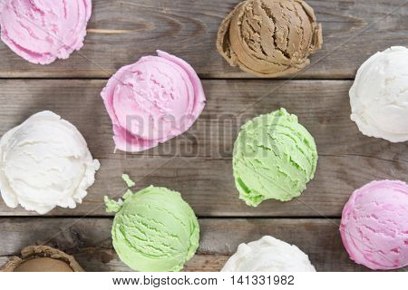 Top view ice cream scoops collection on brown rustic wooden background.