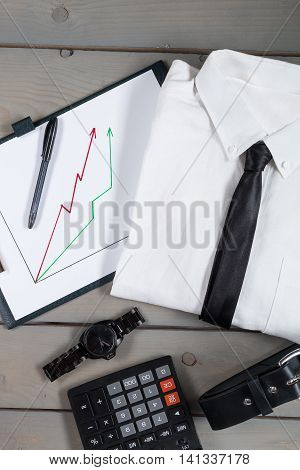 Businessman work outfit on grey wooden background. White shirt with black tie watch belt oxford shoes planchette and calculator. Back to work. Set of mans fashion and accessories. Close up.