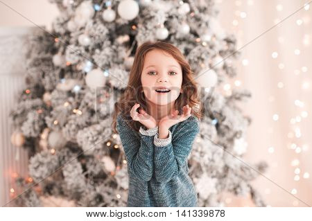 Happy kid girl 4-5 year old laughing in room over christmas tree. Wearing stylish knitted sweater. Looking at camera. Childhood. Christmas time.