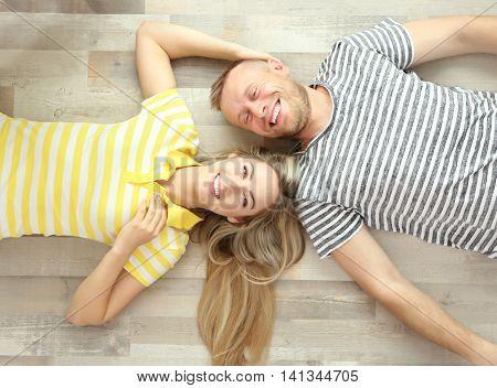 Beautiful couple lying on wooden floor