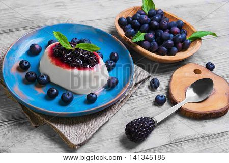 White milky creamy berry pudding with berries blackberries blueberries spoon for pudding worn blue ceramic dish mint leaves on burlap on light wooden background surface rustic