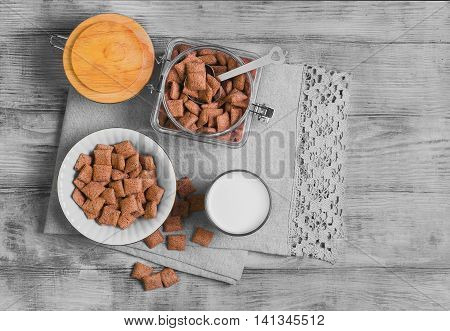 Multigrain healthy cereal corn pads chocolate in white bowl for milk breakfast glass of milk cereal bank cereal is scattered on table light wooden background top view
