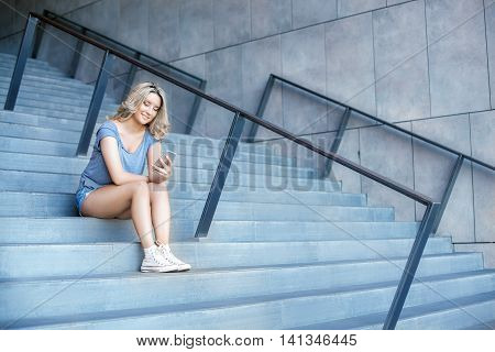Young Girl Working With Mobile Phone And Sitting On Stairs