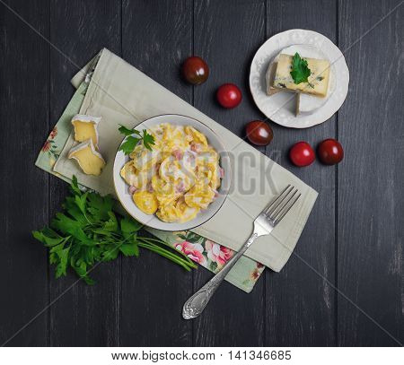 Tortellini with cheese sauce ham ingredients for tortellini cherry tomatoes Camembert cheese blue cheese parsley silver fork on dark black wooden top view