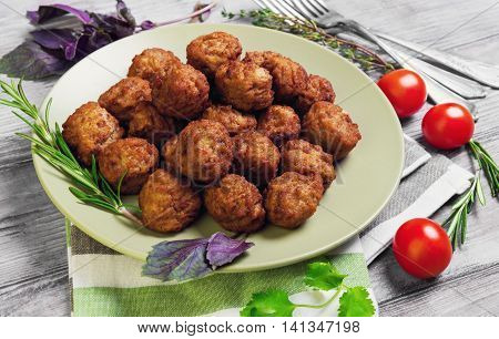 Small meat balls on green plate fresh special spices for meat balls herbs thyme coriander basil rosemary cherry tomatoes silver fork on light white wooden background rustic style