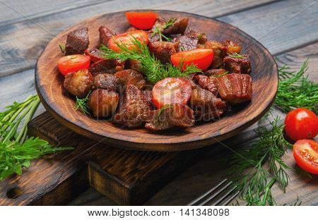 Meat fried small pieces of roast goulash cherry tomatoes lettuce dill a wooden plate for meat goulash rustic style gray wooden background